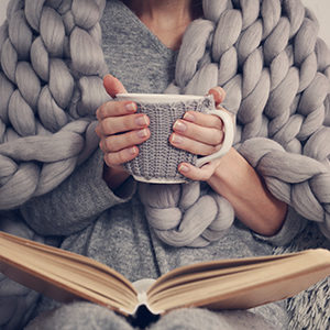 Woman holding coffee with book and blanket