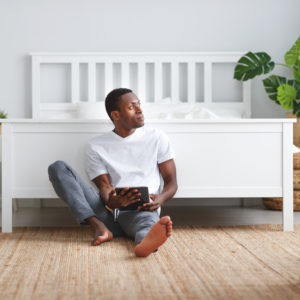 man at foot of bed looking at tablet